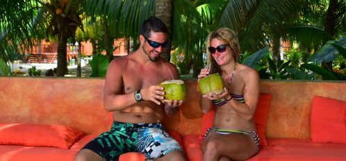Couple drinking coconut water by the pool.