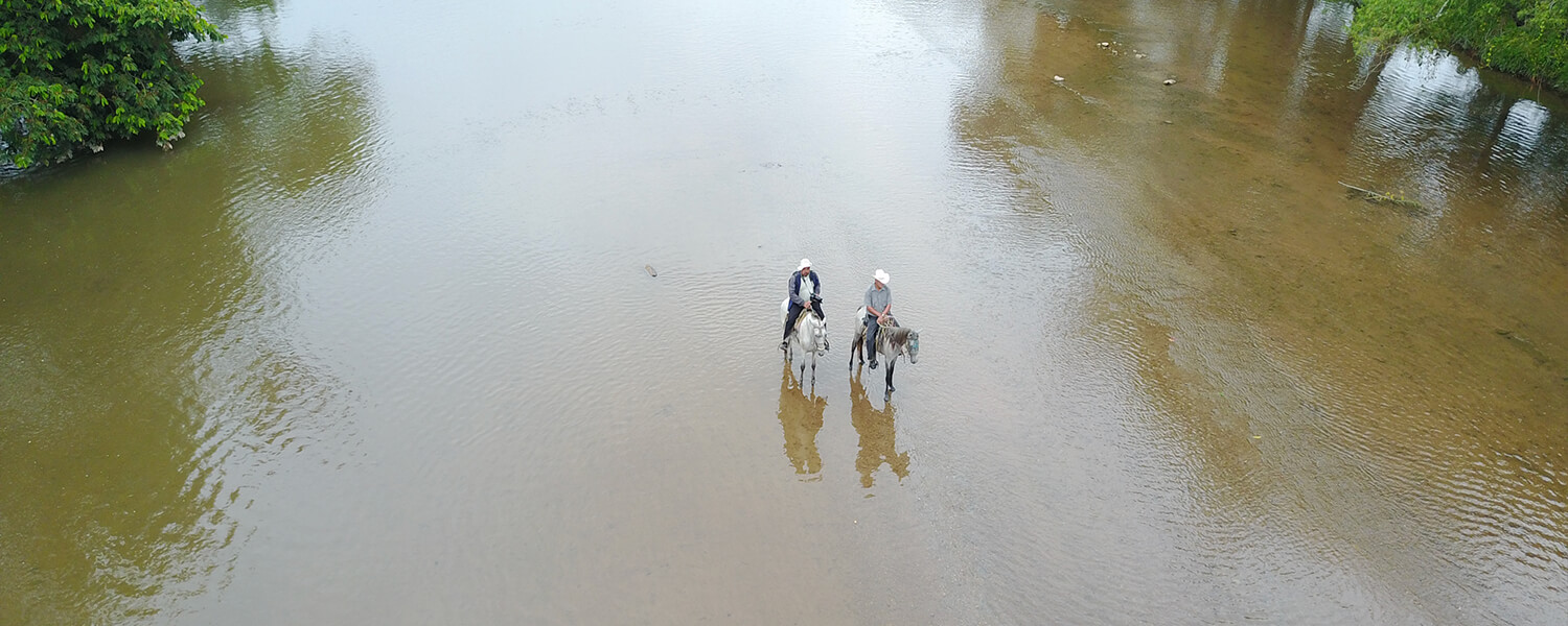 Riding on horseback in a river of Honduras.